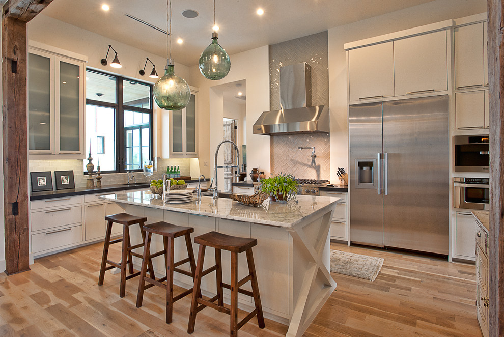 Inspiration for a transitional kitchen remodel in Austin with flat-panel cabinets, stainless steel appliances, marble countertops, white cabinets, gray backsplash and glass tile backsplash