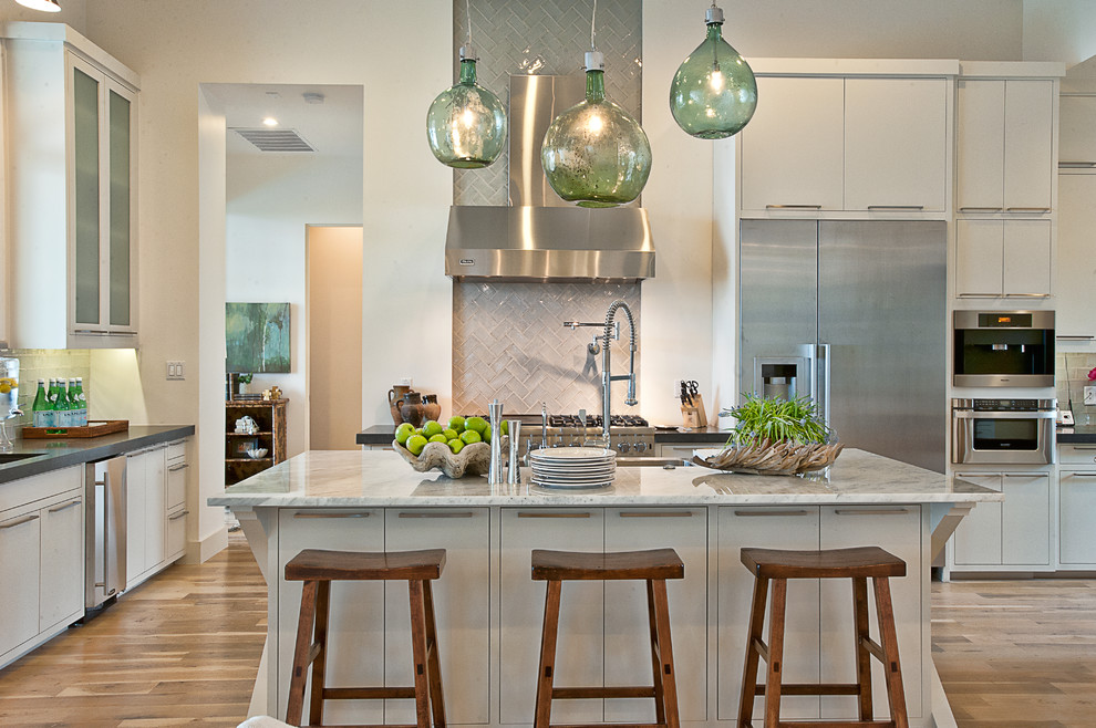 Transitional kitchen photo in Austin with flat-panel cabinets, stainless steel appliances, marble countertops, white cabinets, gray backsplash and glass tile backsplash