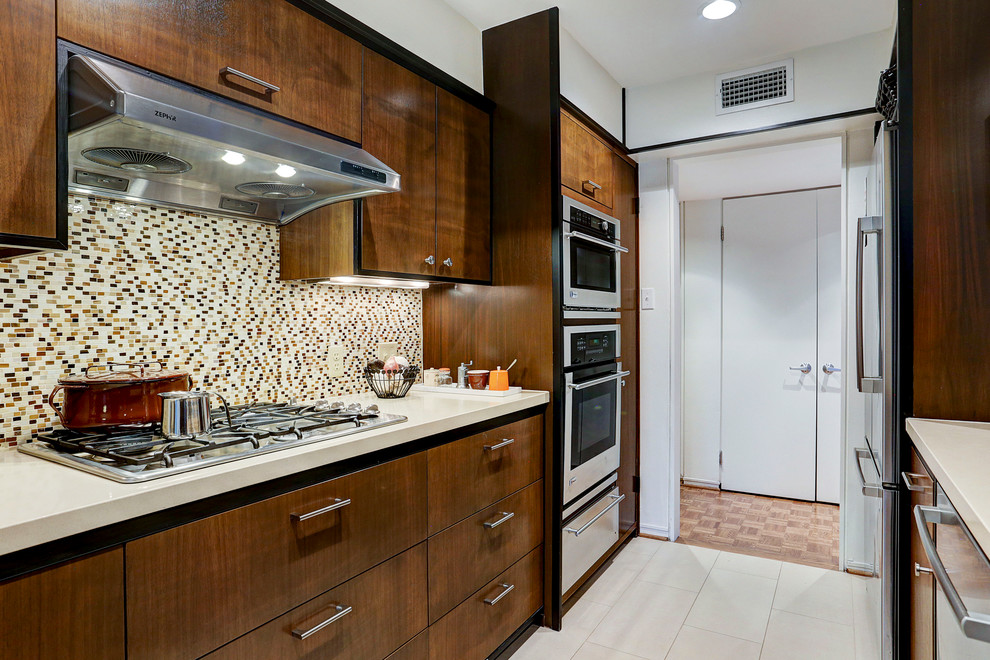 Inspiration for a mid-sized mid-century modern galley porcelain tile and beige floor enclosed kitchen remodel in Houston with flat-panel cabinets, dark wood cabinets, quartz countertops, multicolored backsplash, mosaic tile backsplash, stainless steel appliances and no island