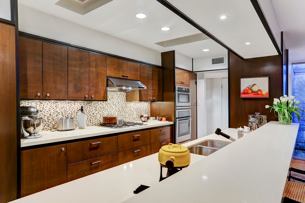 Example of a mid-sized 1950s galley porcelain tile open concept kitchen design in Houston with an undermount sink, flat-panel cabinets, dark wood cabinets, quartzite countertops, multicolored backsplash, mosaic tile backsplash, stainless steel appliances and no island