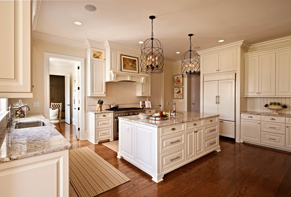 Example of a classic u-shaped kitchen design in Charlotte with an undermount sink, raised-panel cabinets, beige cabinets, beige backsplash and paneled appliances