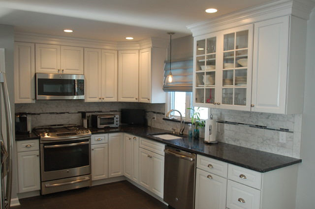 Eat-in kitchen - mid-sized traditional l-shaped ceramic floor and brown floor eat-in kitchen idea in Newark with an undermount sink, white cabinets, subway tile backsplash, stainless steel appliances, raised-panel cabinets, granite countertops, gray backsplash and no island