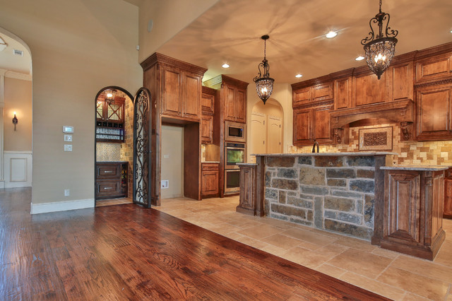Inspiration for a mid-sized timeless galley ceramic floor open concept kitchen remodel in Dallas with an undermount sink, recessed-panel cabinets, medium tone wood cabinets, granite countertops, multicolored backsplash, mosaic tile backsplash, stainless steel appliances and an island