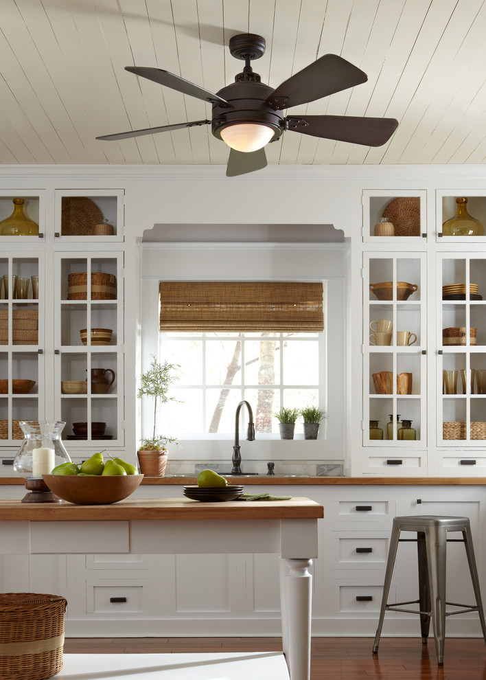 Inspiration for a small rustic galley medium tone wood floor enclosed kitchen remodel in New York with an undermount sink, open cabinets, white cabinets, wood countertops, white backsplash, cement tile backsplash, stainless steel appliances and an island
