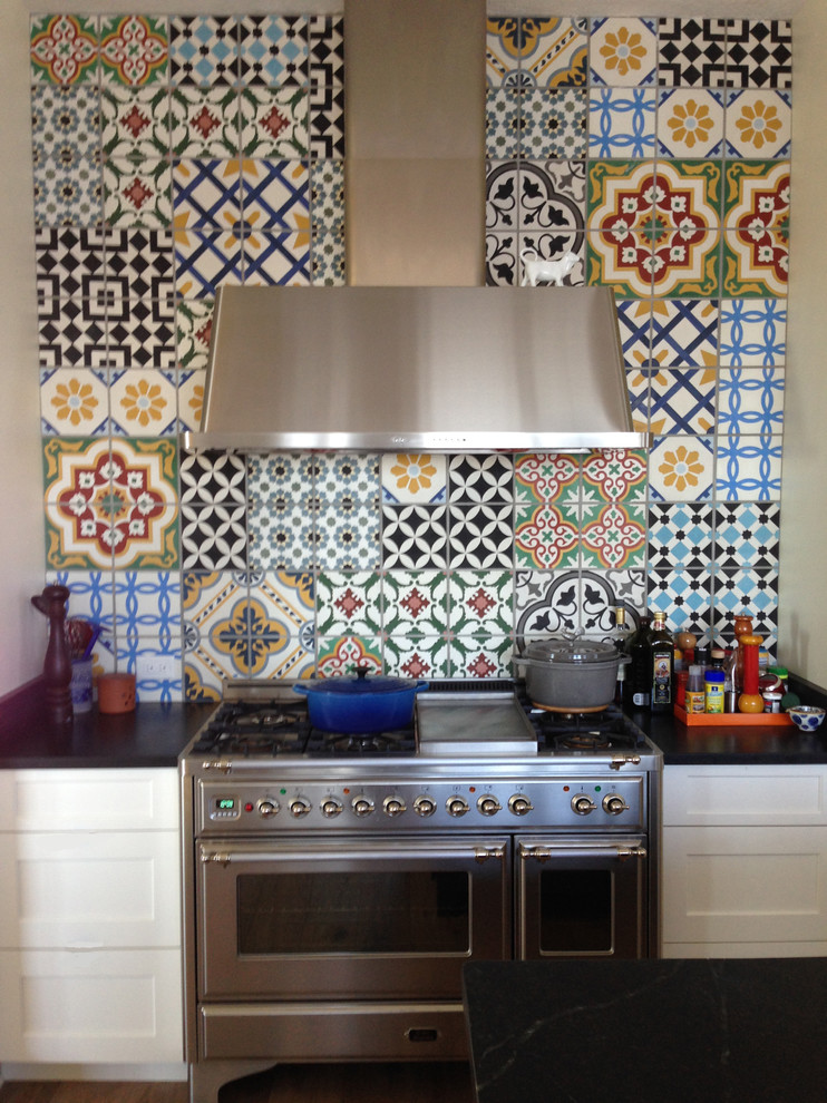 Kitchen - large contemporary kitchen idea in Tampa with white cabinets, cement tile backsplash, stainless steel appliances, marble countertops, black backsplash and an island