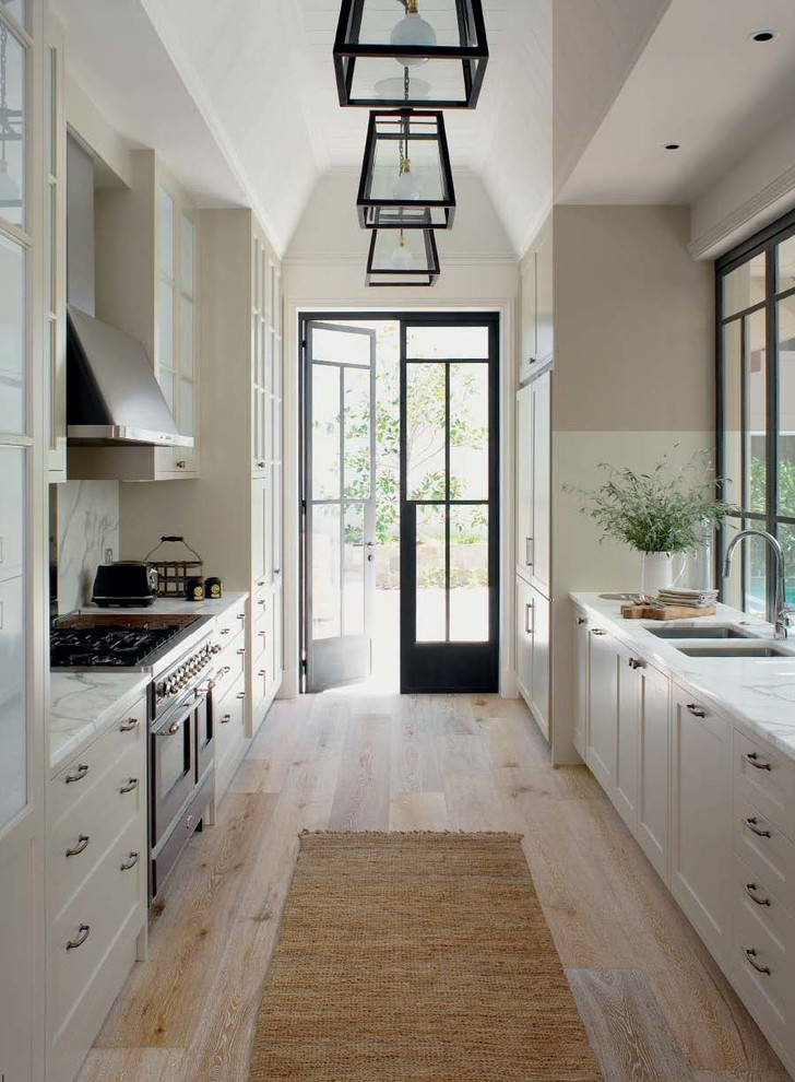 Elegant galley light wood floor kitchen photo in Central Coast with a double-bowl sink, shaker cabinets, white cabinets, marble countertops, white backsplash and no island