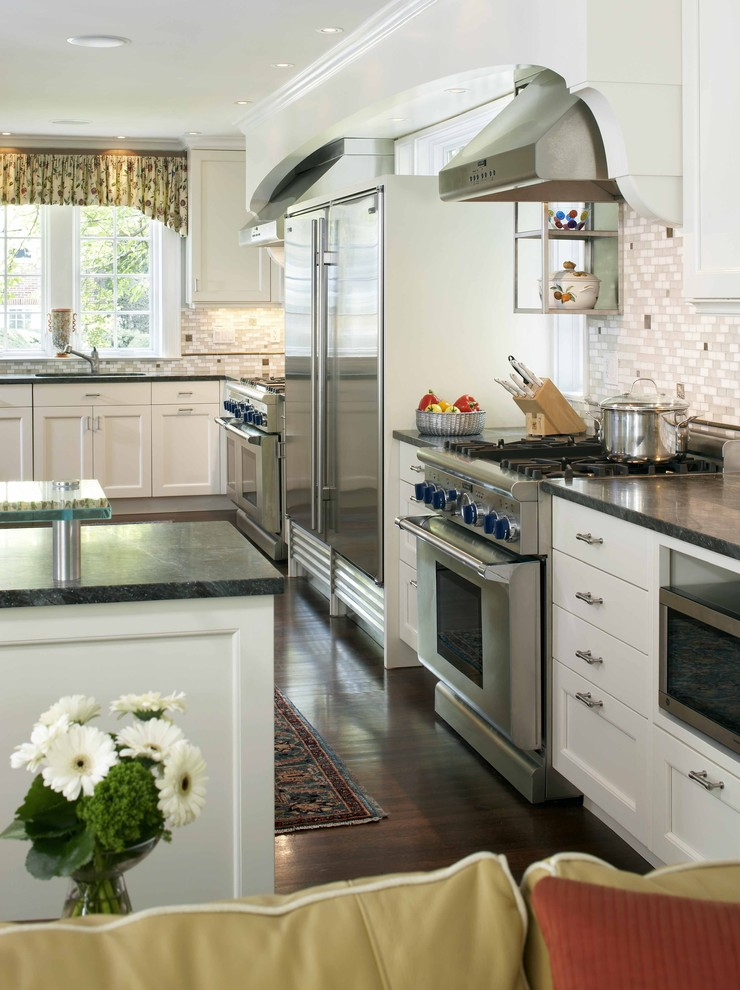 Kitchen - traditional l-shaped kitchen idea in Boston with soapstone countertops, stainless steel appliances, white cabinets and gray backsplash