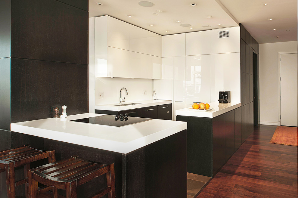 Inspiration for a mid-sized modern medium tone wood floor and brown floor kitchen remodel in New York with a double-bowl sink, flat-panel cabinets, white cabinets, quartz countertops, white backsplash, stainless steel appliances and an island