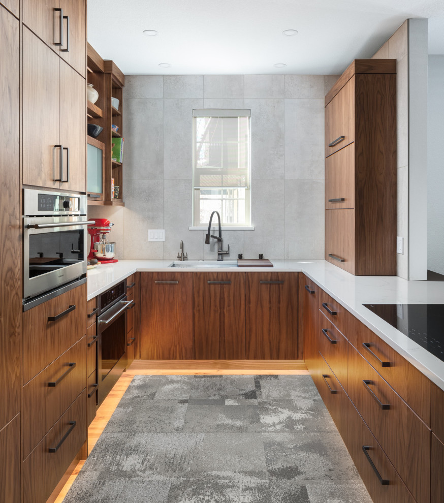 Example of a mid-sized trendy u-shaped medium tone wood floor open concept kitchen design in Denver with an undermount sink, flat-panel cabinets, medium tone wood cabinets, quartz countertops, gray backsplash, ceramic backsplash, stainless steel appliances, a peninsula and white countertops