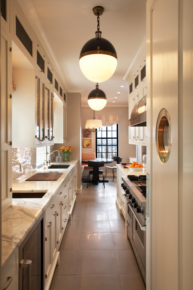 Inspiration for a transitional galley enclosed kitchen remodel in New York with glass-front cabinets, marble countertops and stainless steel appliances