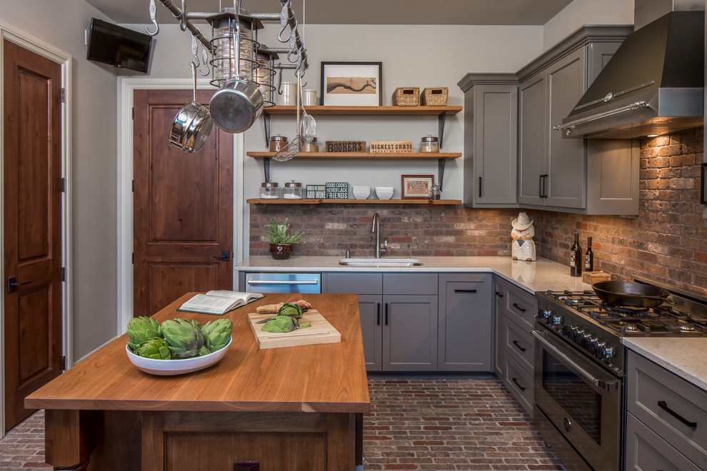 Large transitional l-shaped brick floor and brown floor enclosed kitchen photo in Austin with an undermount sink, gray cabinets, solid surface countertops, stainless steel appliances, an island, shaker cabinets, brick backsplash and brown backsplash