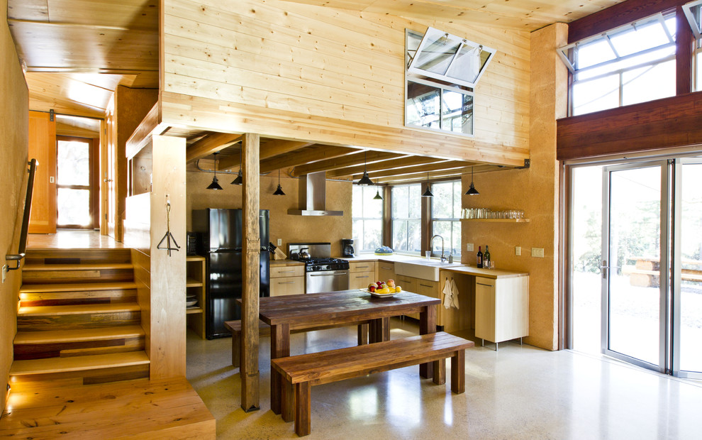 Eat-in kitchen - small rustic l-shaped concrete floor eat-in kitchen idea in Sacramento with a farmhouse sink, flat-panel cabinets, light wood cabinets, black appliances, wood countertops and no island