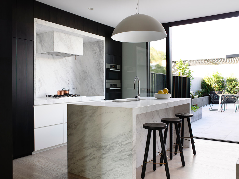 Danish galley light wood floor kitchen photo in Melbourne with a double-bowl sink, flat-panel cabinets, white cabinets, white backsplash, stainless steel appliances and an island