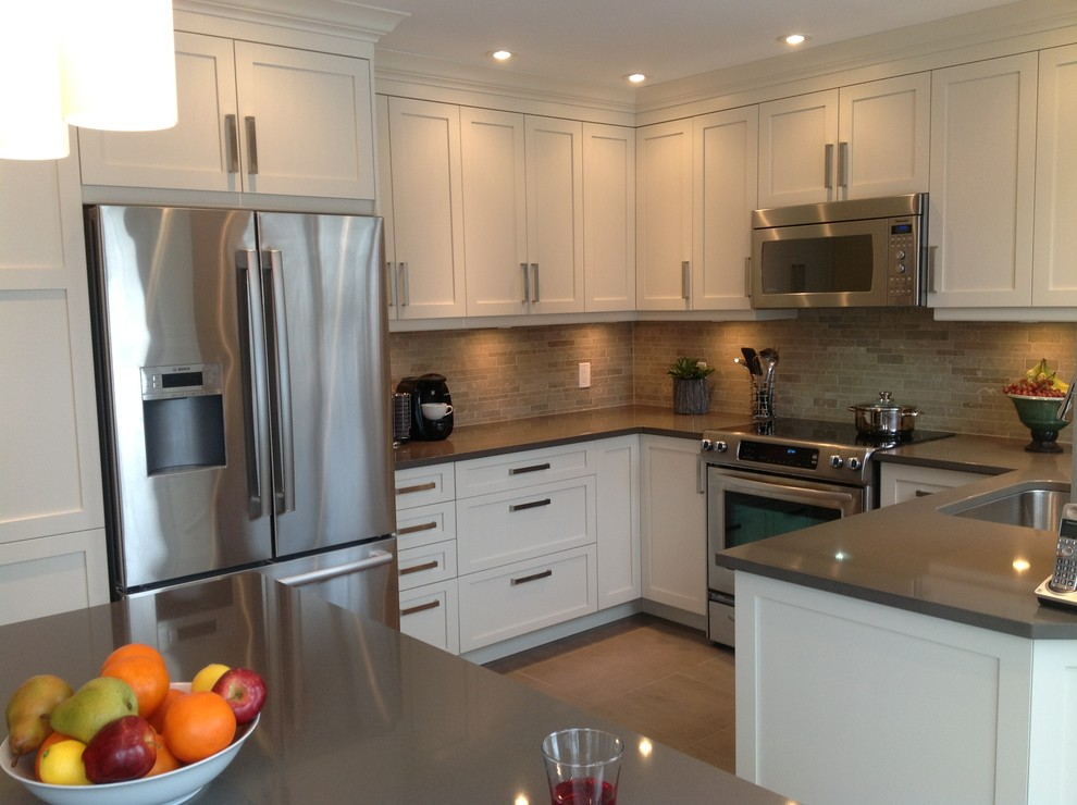 Enclosed kitchen - contemporary u-shaped enclosed kitchen idea in Montreal with a single-bowl sink, shaker cabinets, white cabinets, quartz countertops, beige backsplash, stone tile backsplash and stainless steel appliances