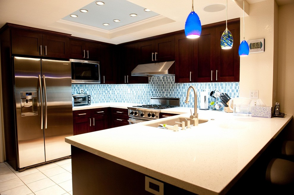 Inspiration for a contemporary u-shaped kitchen remodel in New York with a double-bowl sink, shaker cabinets, dark wood cabinets, blue backsplash, stainless steel appliances and no island