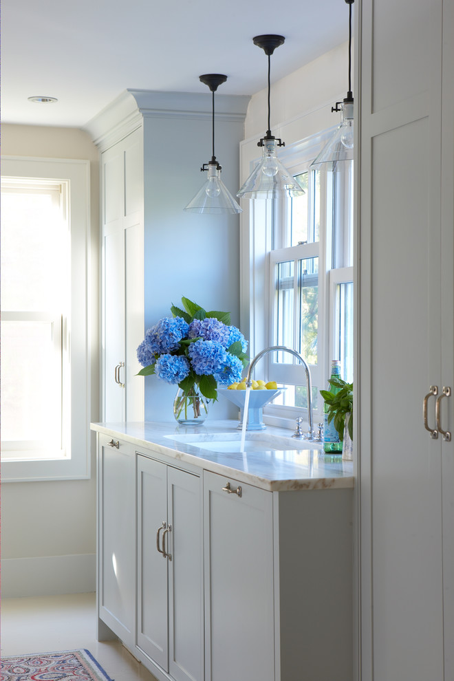 Mid-sized transitional galley porcelain tile and beige floor enclosed kitchen photo in Boston with an undermount sink, shaker cabinets, white cabinets, quartzite countertops, paneled appliances and no island