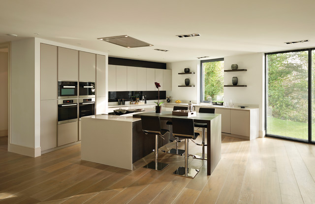 This is an example of a modern l-shaped open plan kitchen in Other with a submerged sink, shaker cabinets, white cabinets, composite countertops, stone slab splashback, stainless steel appliances and an island.