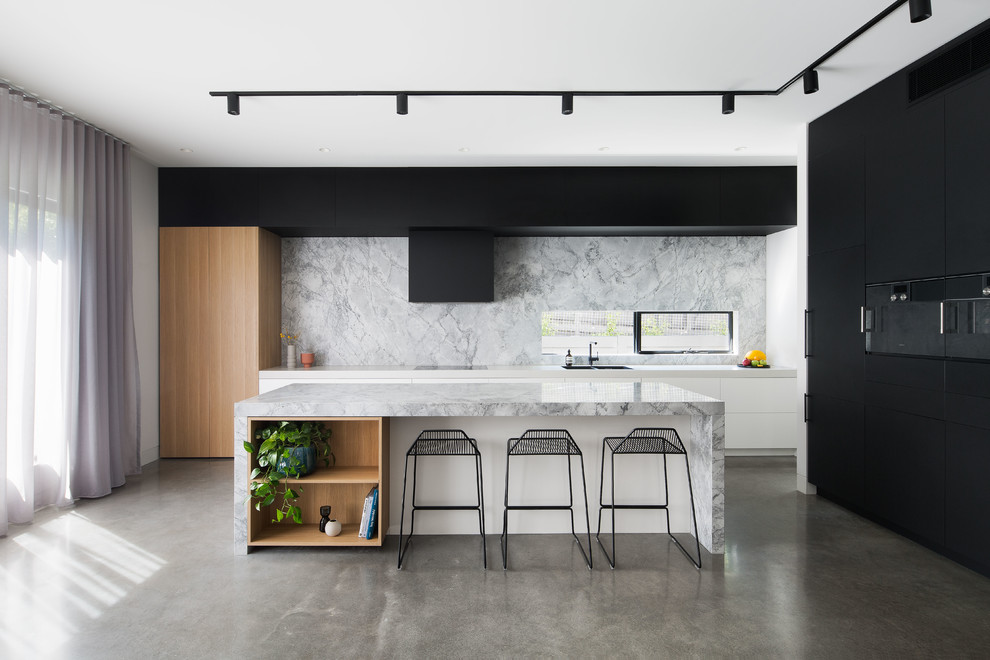 Example of a danish l-shaped concrete floor and gray floor kitchen design in Melbourne with a double-bowl sink, flat-panel cabinets, white backsplash, black appliances, an island and white countertops