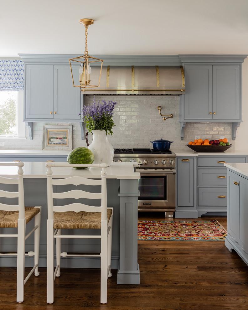 Elegant dark wood floor kitchen photo in San Francisco with beaded inset cabinets, blue cabinets, gray backsplash, subway tile backsplash, stainless steel appliances and an island