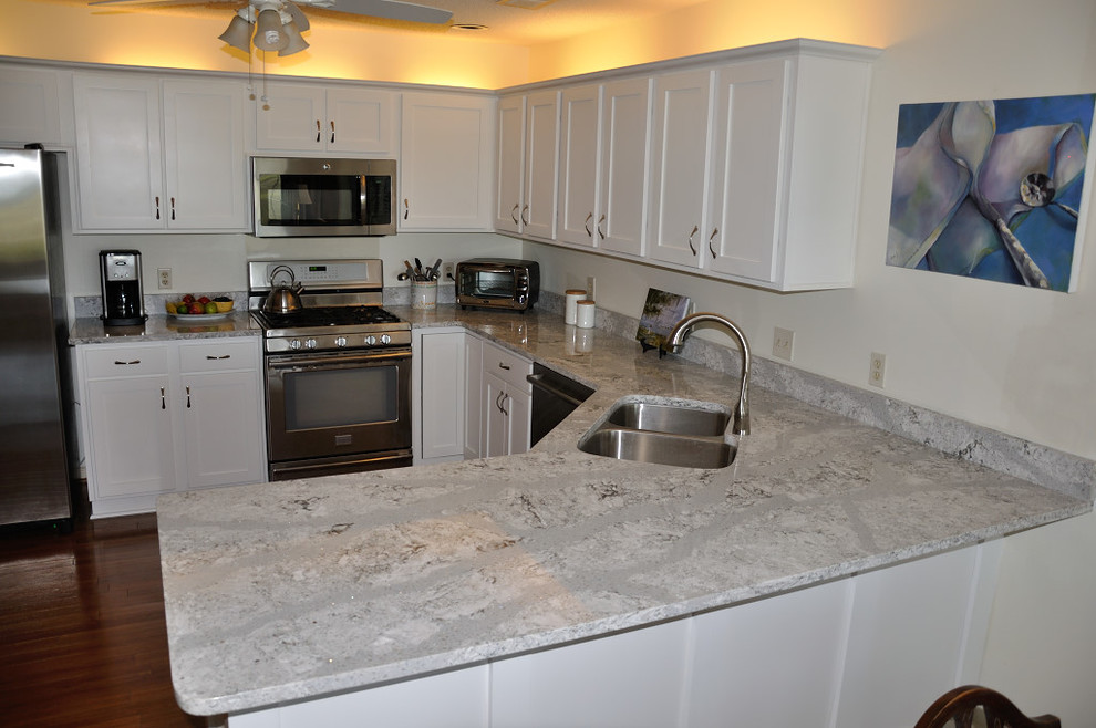 Inspiration for a mid-sized timeless l-shaped eat-in kitchen remodel in Atlanta with an undermount sink, raised-panel cabinets, white cabinets, quartz countertops, stainless steel appliances and no island