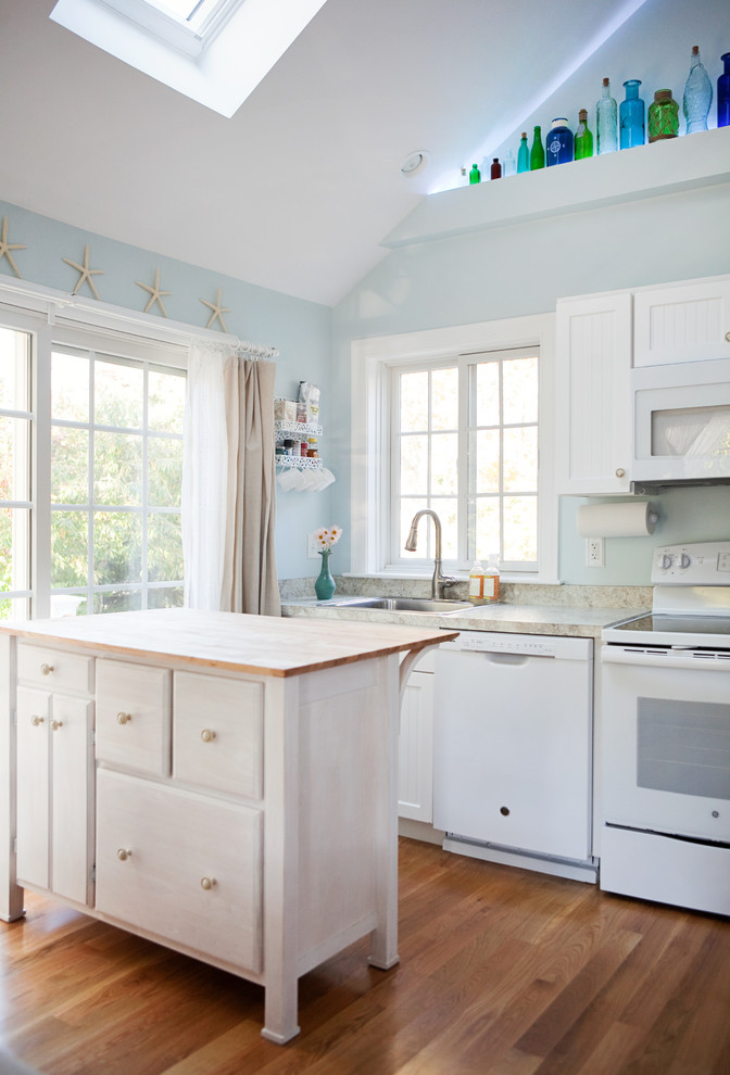 Coastal medium tone wood floor kitchen photo in Boston with shaker cabinets, white cabinets, white appliances and an island