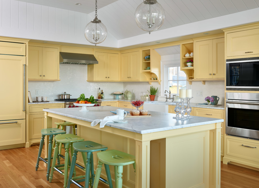 Kitchen - coastal l-shaped light wood floor kitchen idea in Boston with a farmhouse sink, yellow cabinets, marble countertops, white backsplash, paneled appliances, an island, white countertops and recessed-panel cabinets