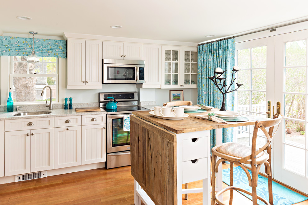 Beach style medium tone wood floor and brown floor kitchen photo in Boston with an undermount sink, shaker cabinets, white cabinets, stainless steel appliances, an island and gray countertops