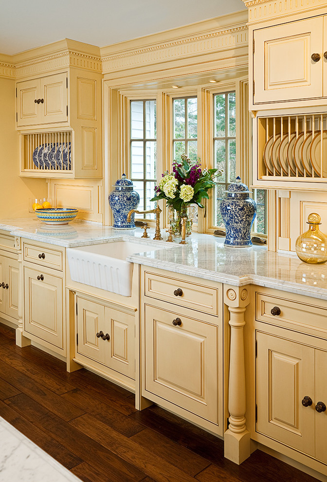 Elegant dark wood floor eat-in kitchen photo in Bridgeport with a farmhouse sink, marble countertops, beaded inset cabinets, yellow cabinets and an island
