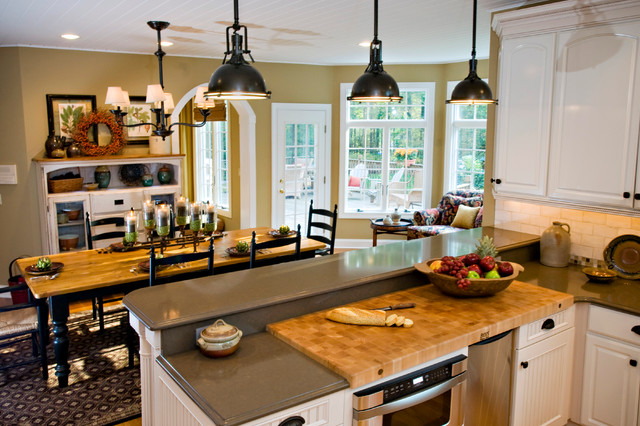 Inspiration for a country u-shaped medium tone wood floor eat-in kitchen remodel in New York with an undermount sink, white cabinets, granite countertops, white backsplash, subway tile backsplash, stainless steel appliances and an island