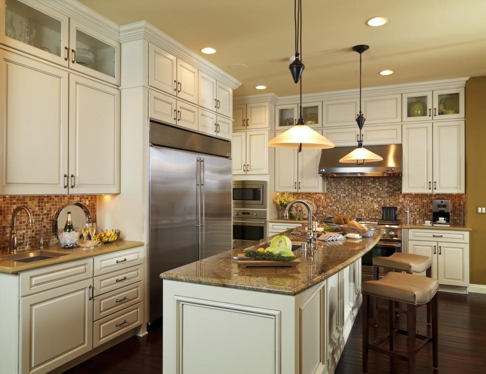 Elegant brown floor kitchen photo in Las Vegas with mosaic tile backsplash, brown backsplash, raised-panel cabinets and stainless steel appliances