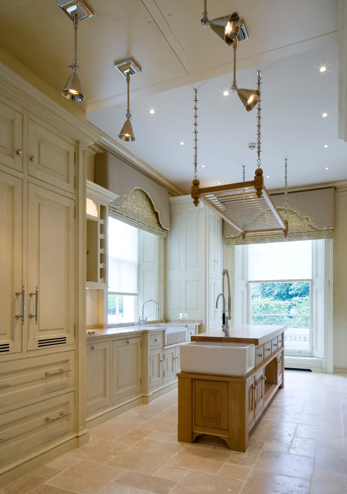 Inspiration for a timeless kitchen remodel in London with raised-panel cabinets and an island