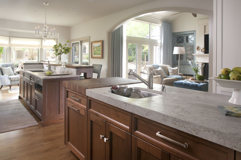 Transitional open concept kitchen photo in Denver with an undermount sink, recessed-panel cabinets, dark wood cabinets and granite countertops