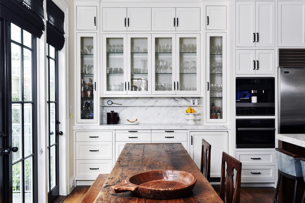 Eat-in kitchen - transitional dark wood floor and brown floor eat-in kitchen idea in San Francisco with recessed-panel cabinets, white backsplash, stainless steel appliances, marble countertops, marble backsplash and an island