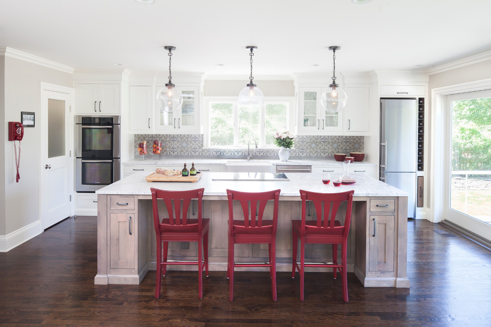 Kitchen - traditional galley dark wood floor kitchen idea in New York with a farmhouse sink, shaker cabinets, white cabinets, marble countertops, gray backsplash, cement tile backsplash, stainless steel appliances and an island
