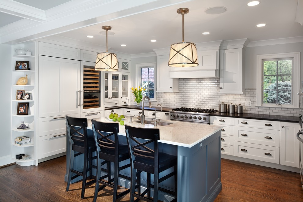 Elegant u-shaped dark wood floor kitchen photo in DC Metro with an undermount sink, shaker cabinets, white cabinets, white backsplash, subway tile backsplash, paneled appliances and an island