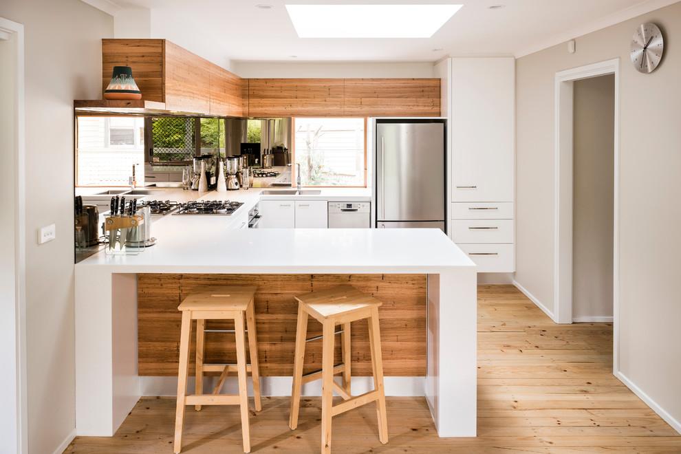 Kleine Moderne Wohnküche ohne Insel in U-Form mit Doppelwaschbecken, weißen Schränken, Mineralwerkstoff-Arbeitsplatte, Rückwand aus Spiegelfliesen und Küchengeräten aus Edelstahl in Melbourne