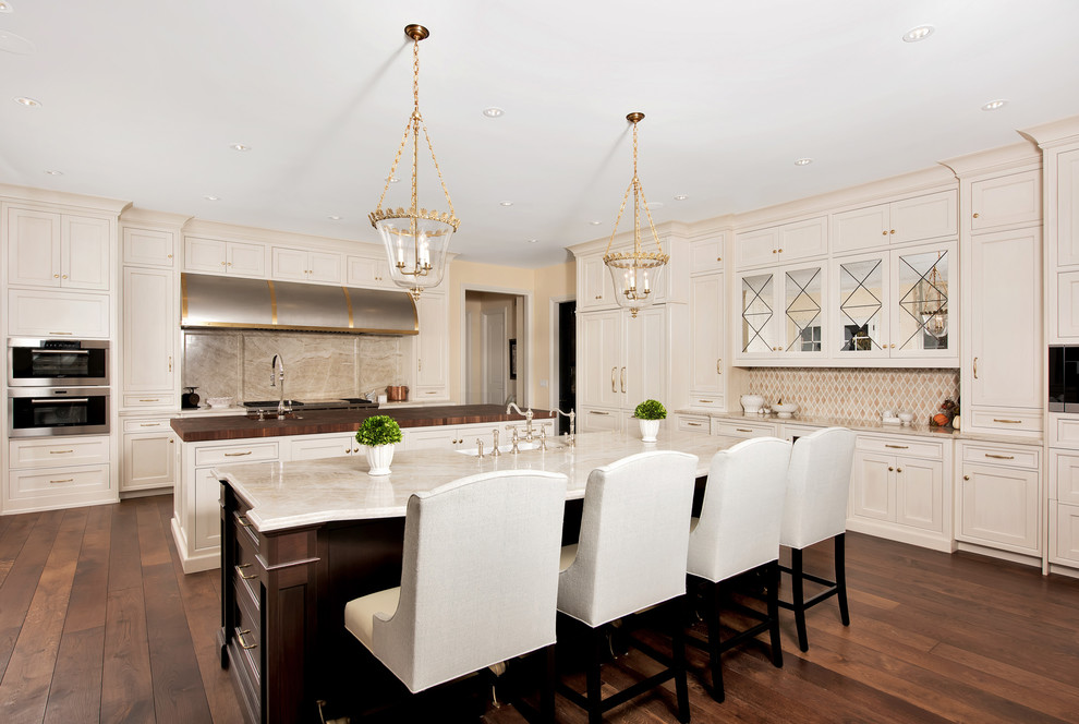 Example of a huge classic u-shaped dark wood floor and brown floor eat-in kitchen design in Chicago with shaker cabinets, beige cabinets, beige backsplash, two islands, an undermount sink, marble countertops, stone slab backsplash and stainless steel appliances