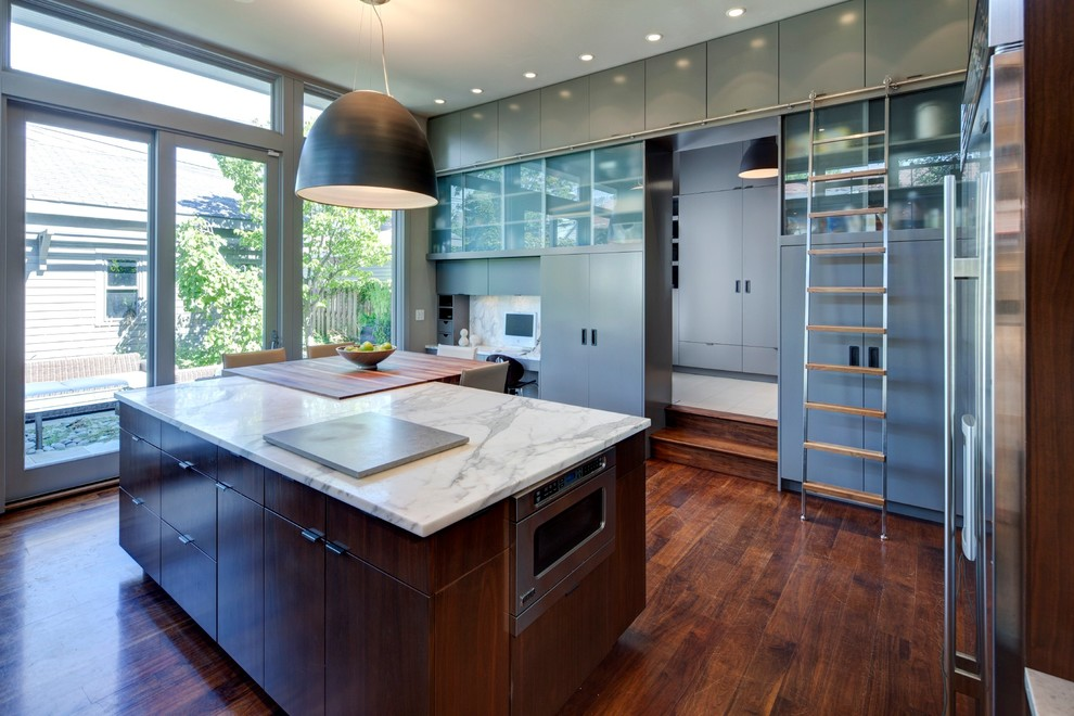 Trendy enclosed kitchen photo in Chicago with flat-panel cabinets, gray cabinets and stone slab backsplash