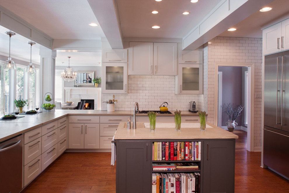 Example of a huge trendy u-shaped medium tone wood floor and brown floor open concept kitchen design in Austin with stainless steel appliances, an undermount sink, shaker cabinets, white cabinets, concrete countertops, white backsplash, subway tile backsplash and an island