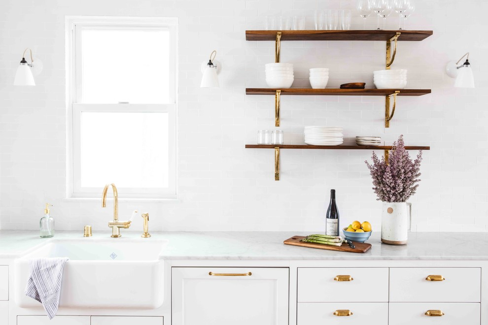 Eat-in kitchen - mid-sized transitional single-wall light wood floor eat-in kitchen idea in San Francisco with a farmhouse sink, flat-panel cabinets, white cabinets, marble countertops, white backsplash, ceramic backsplash, white appliances and an island