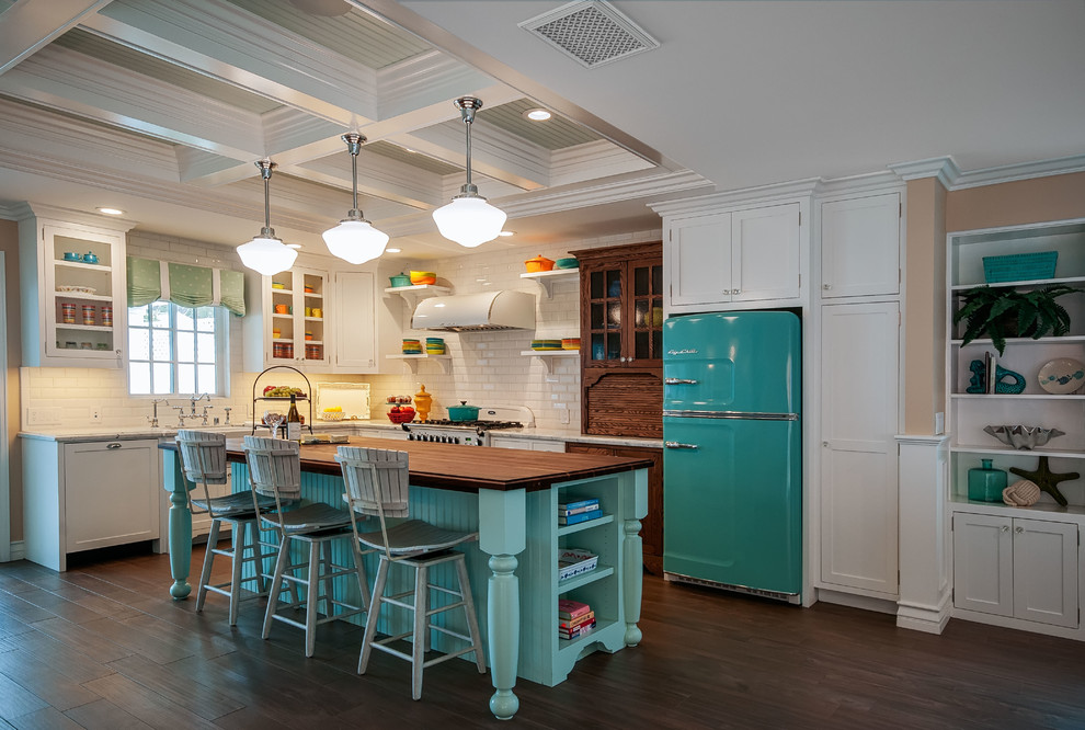 Example of a mid-sized beach style l-shaped kitchen design in San Diego with a farmhouse sink, white backsplash, subway tile backsplash, colored appliances and an island