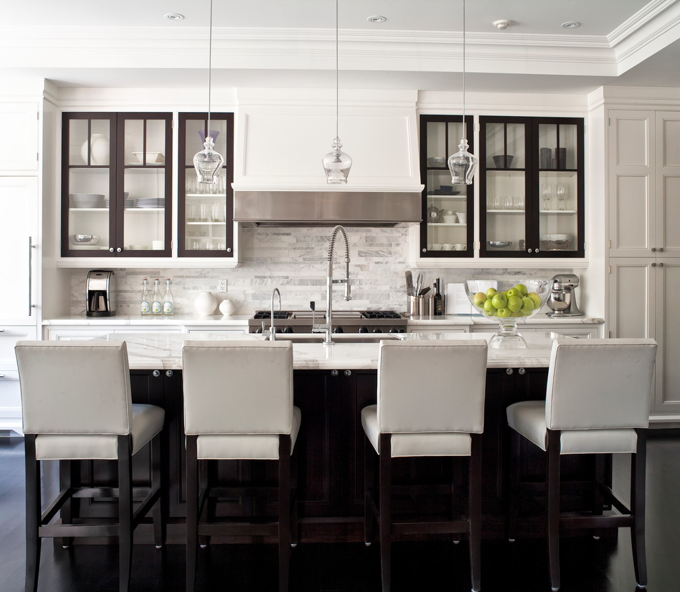 Example of a transitional galley kitchen design in Toronto with white backsplash, marble countertops, an undermount sink, white cabinets, glass-front cabinets, paneled appliances, marble backsplash and white countertops