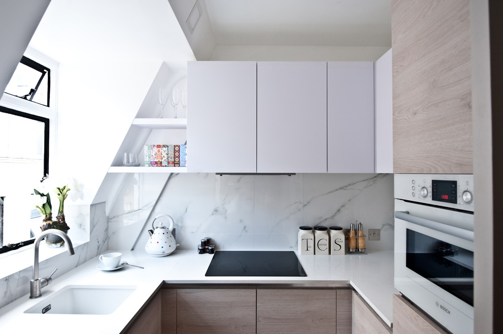 Small trendy u-shaped kitchen photo in London with an undermount sink, flat-panel cabinets, white cabinets, quartz countertops, white backsplash, white appliances, no island and stone slab backsplash