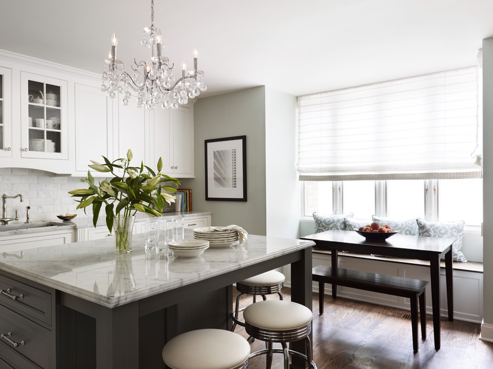 Eat-in kitchen - mid-sized traditional l-shaped dark wood floor and brown floor eat-in kitchen idea in Chicago with an undermount sink, white cabinets, marble countertops, white backsplash, marble backsplash, an island and beaded inset cabinets