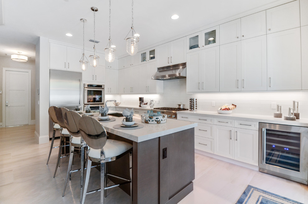 Example of a large transitional l-shaped beige floor kitchen design in Miami with shaker cabinets, white cabinets, white backsplash, stainless steel appliances and an island