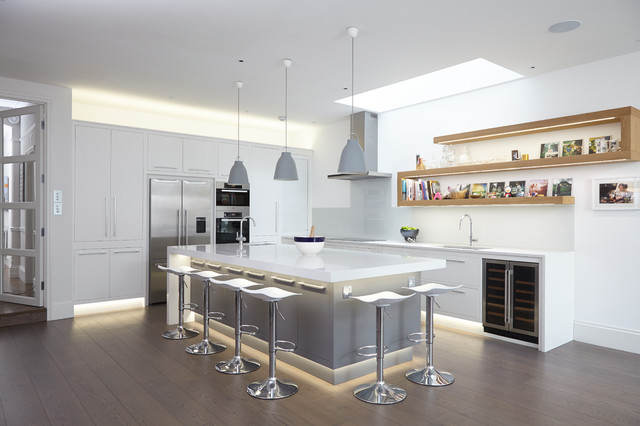 Kitchen - contemporary l-shaped medium tone wood floor kitchen idea in London with an undermount sink, flat-panel cabinets, white cabinets, white backsplash, glass sheet backsplash, stainless steel appliances and an island