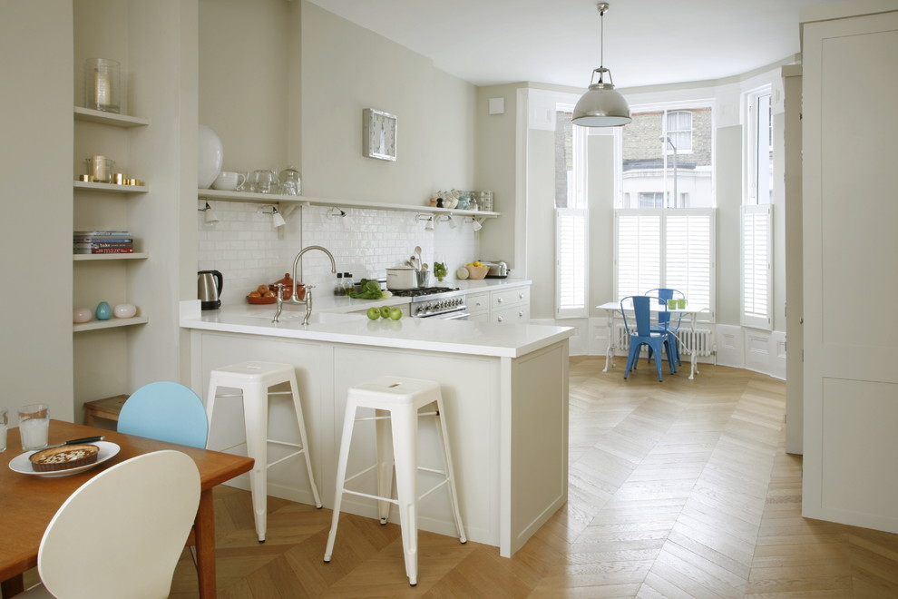 Inspiration for a mid-sized timeless l-shaped medium tone wood floor eat-in kitchen remodel in London with an undermount sink, white cabinets, solid surface countertops, white backsplash, subway tile backsplash, stainless steel appliances, a peninsula and open cabinets
