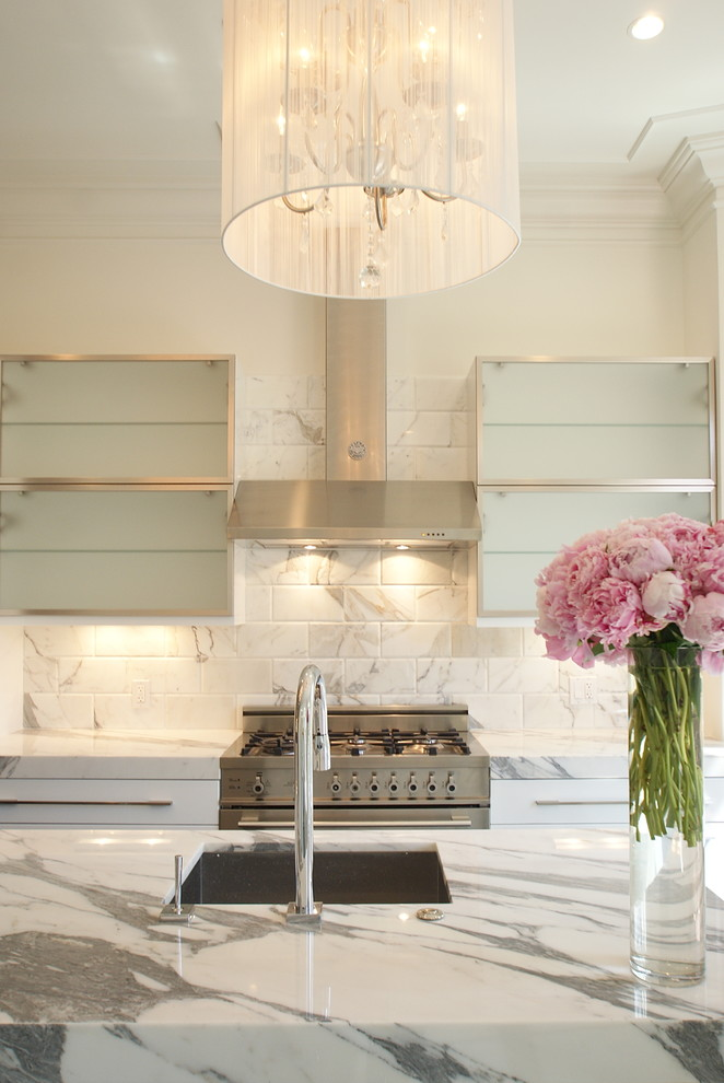 Trendy kitchen photo in Boston with stainless steel appliances, marble countertops, a single-bowl sink, glass-front cabinets, white backsplash and marble backsplash