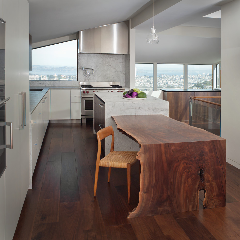 Example of a trendy l-shaped dark wood floor kitchen design in San Francisco with flat-panel cabinets, white cabinets, white backsplash, stainless steel appliances and an island