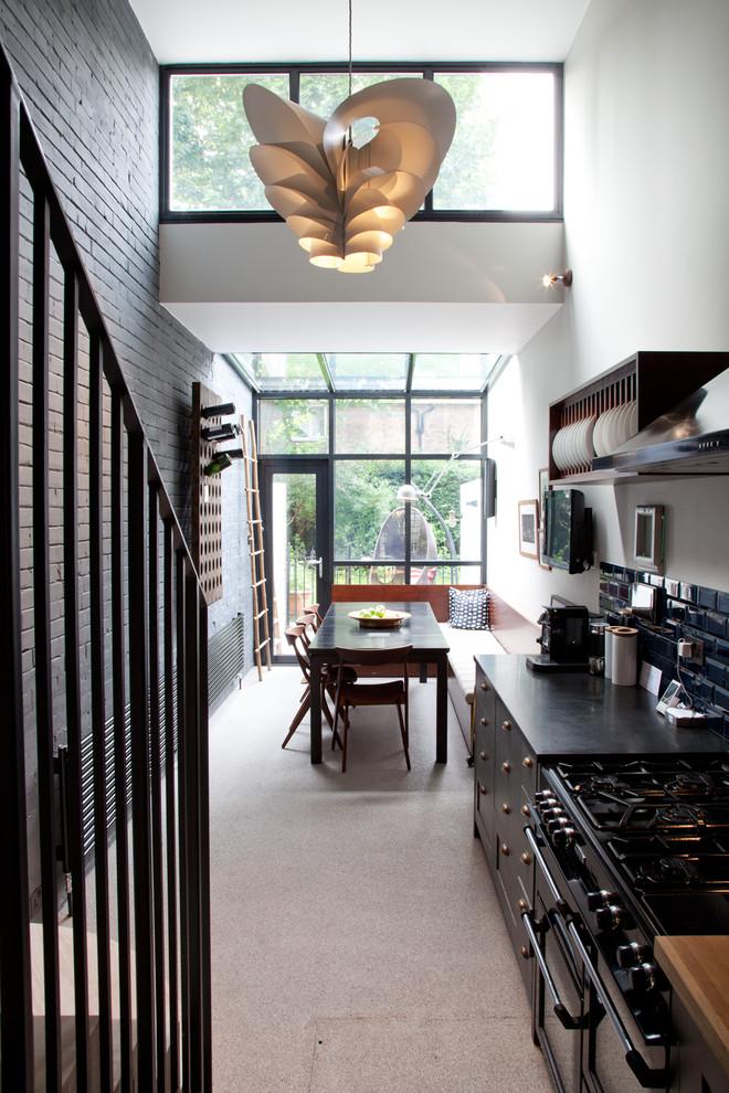 Urban single-wall eat-in kitchen photo in London with blue backsplash, subway tile backsplash and black appliances